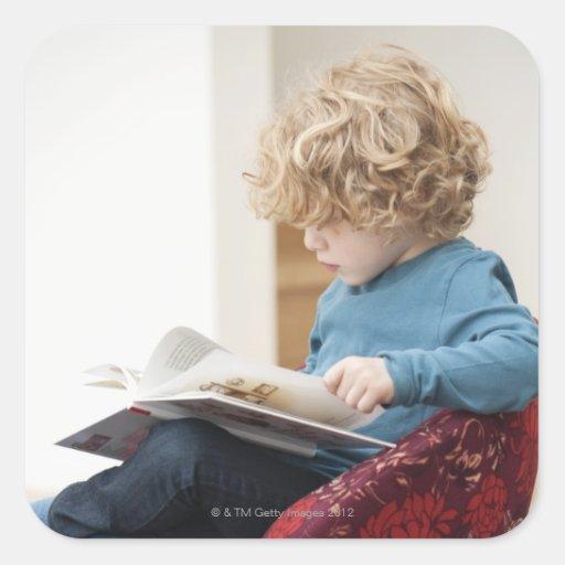 Boy reading a book square sticker