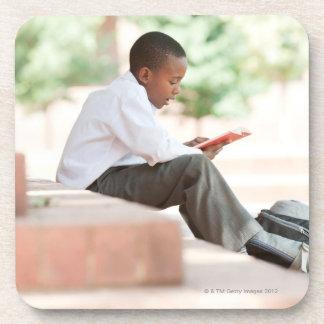 Boy reading on steps outside school, drink coaster