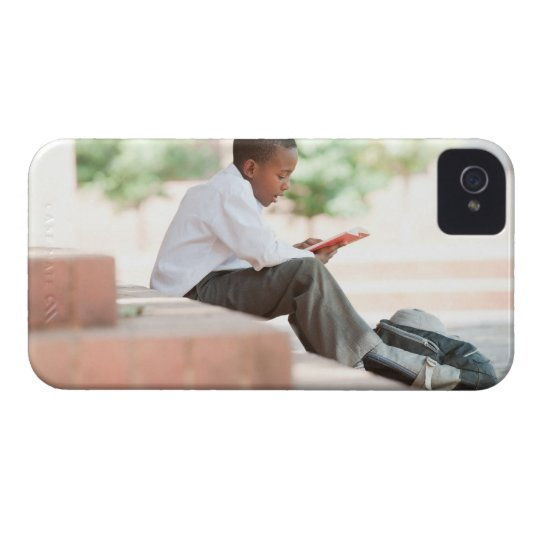 Boy reading on steps outside school, iPhone 4 cover