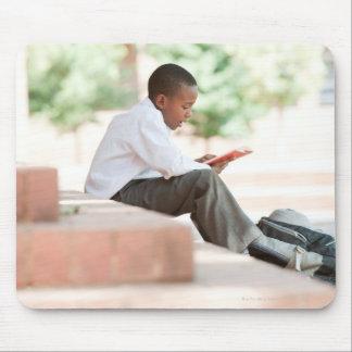 Boy reading on steps outside school, mousepad