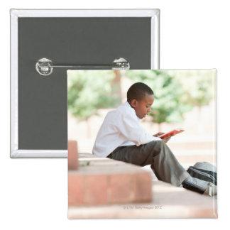 Boy reading on steps outside school, pinback button