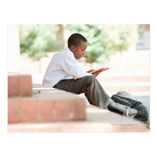 Boy reading on steps outside school, postcard