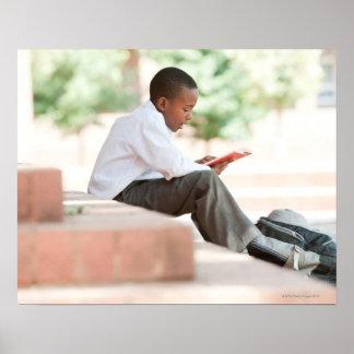 Boy reading on steps outside school, poster