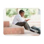 Boy reading on steps outside school, vinyl magnet
