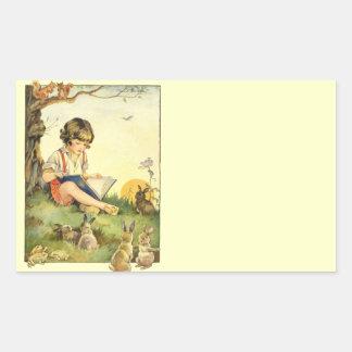 Boy reading under tree with rabbits rectangular sticker