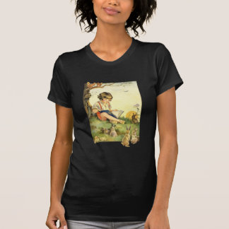 Boy reading under tree with rabbits shirt