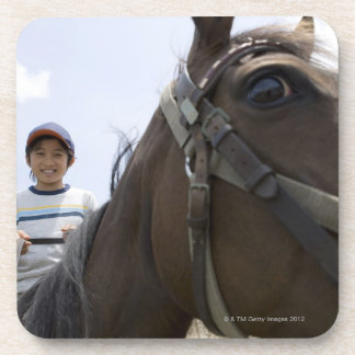 Boy riding a horse drink coaster