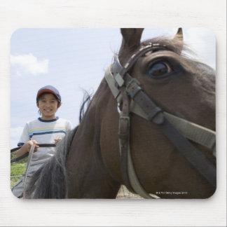 Boy riding a horse mouse pad