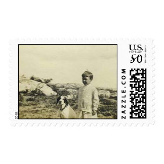 Boy standing by his dog at the beach postage