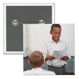 Boy standing in front of class reading in 2 pin
