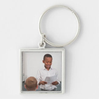 Boy standing in front of class reading in 2 keychains