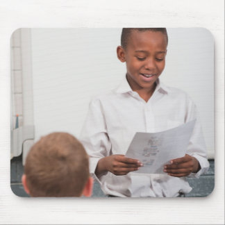 Boy standing in front of class reading in 2 mouse pad