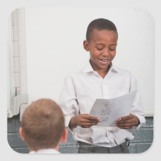 Boy standing in front of class reading in 2 square sticker