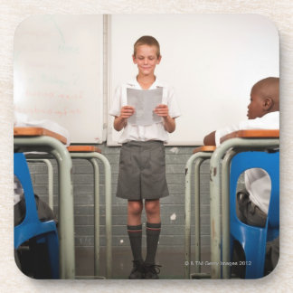 Boy standing in front of class reading in beverage coaster