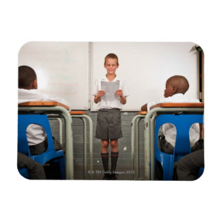 Boy standing in front of class reading in flexible magnets
