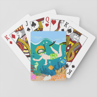 Boy swimming and diving with tropical fish playing cards
