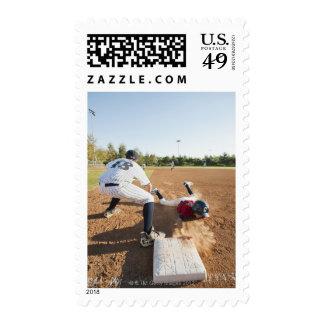 Boys (10-11) playing baseball postage