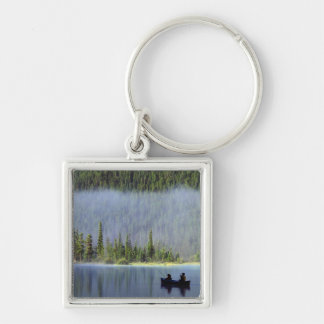 Boys fishing from canoe with mist in keychain