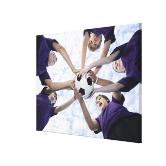 Boys holding soccer ball in huddle canvas print
