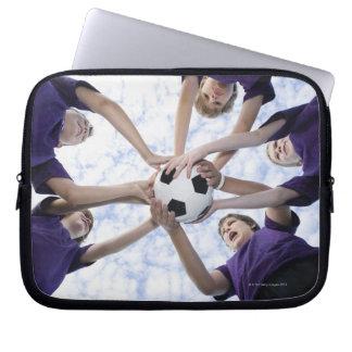 Boys holding soccer ball in huddle laptop sleeves