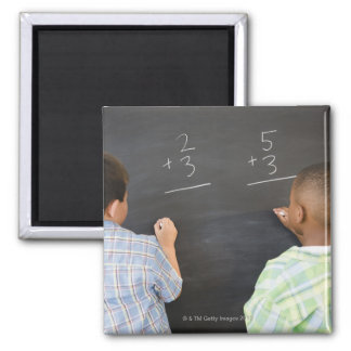 Boys solving math problems on blackboard 2 inch square magnet