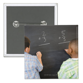 Boys solving math problems on blackboard buttons