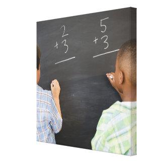 Boys solving math problems on blackboard canvas print