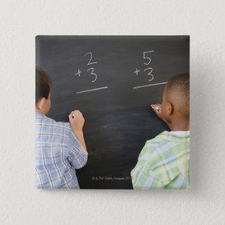 Boys solving math problems on blackboard pinback button