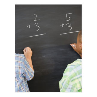 Boys solving math problems on blackboard postcard