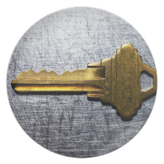 Brass key on stainless steel dinner plate