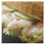 Bread roll filled with shrimps, cucumber and large square tile