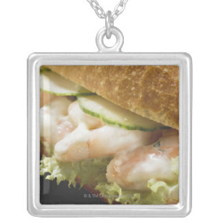 Bread roll filled with shrimps, cucumber and silver plated necklace