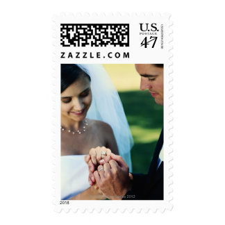 Bride and groom holding hands, close-up postage