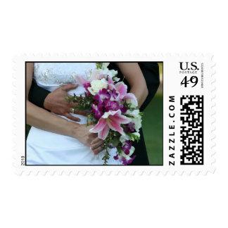 bride holding flowers groom behind painting postage stamps