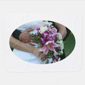 bride holding flowers groom behind painting stroller blanket