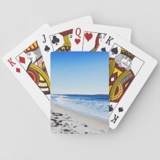 Bright blue waters and blinding sun on beach playing cards