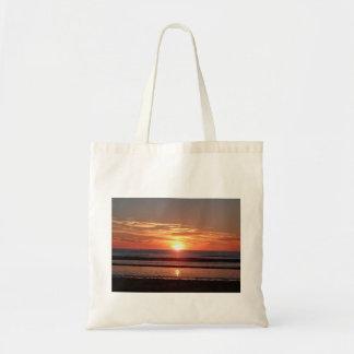 Bright orange sunny sunset seaside view tote bag