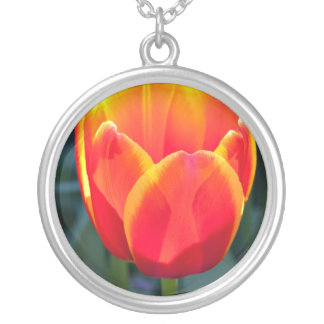 Bright red and yellow tulip bloom on green round pendant necklace