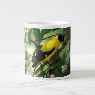 Bright yellow and black bird in tree large coffee mug