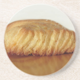 Brioche on a wooden table with granulated sugar coaster