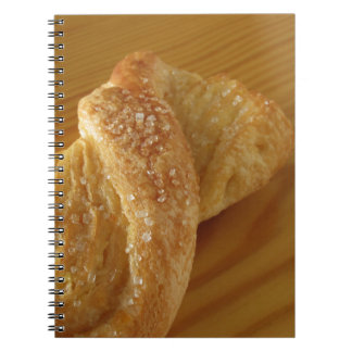 Brioche on a wooden table with granulated sugar notebook