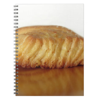 Brioche on a wooden table with granulated sugar spiral notebook