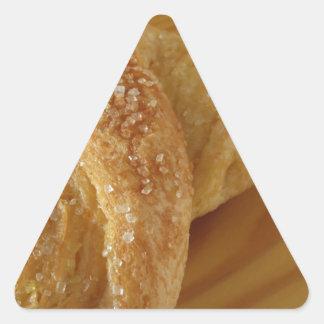 Brioche on a wooden table with granulated sugar triangle sticker