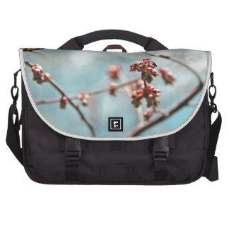 Brotes rosados de la primavera en azul bolsas de portatil