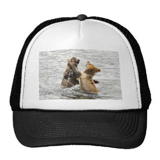 Brown bear cubs playing in water mesh hats