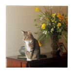 "Brown black Tabby cat Sitting on piano flowers Tile<br><div class=""desc"">Brown black Tabby cat Sitting on piano flowers. My cat sitting on a piano with a bouquet of flowers behind her. She was posing for me</div>"