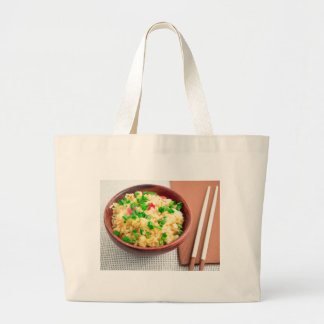 Brown bowl with a portion of cooked rice large tote bag