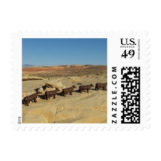 Brown cows walking in desert postage