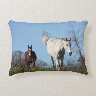 Brown horse follows white horse over a hill accent pillow