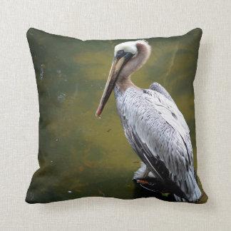 brown pelican near green water fish swimming throw pillow